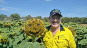 Man standing in field of sunflowers one flower has a smiley face